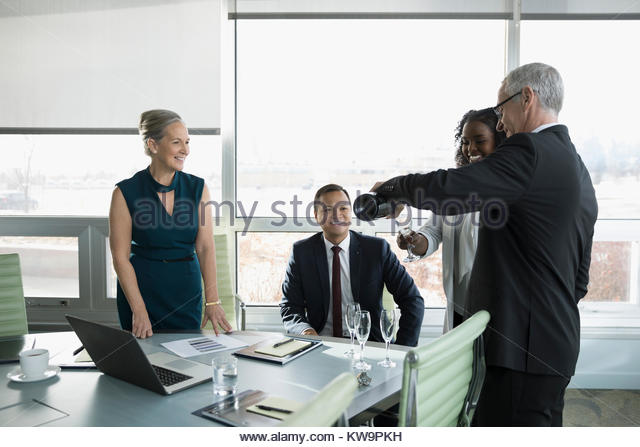 Businessman pouring champagne for colleagues,celebrating in conference room meeting - Stock Image