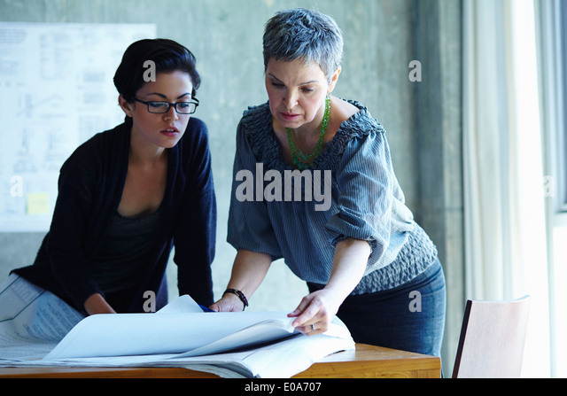 Two businesswomen checking blue prints in office - Stock Image