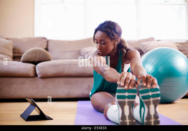 Young woman exercising on sitting room floor whilst looking at digital tablet - Stock-Bilder