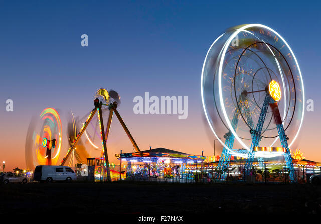 Colorful carnival Ferris wheel and gondola spinning in motion blurred at twilight in an amusement park - Stock Image