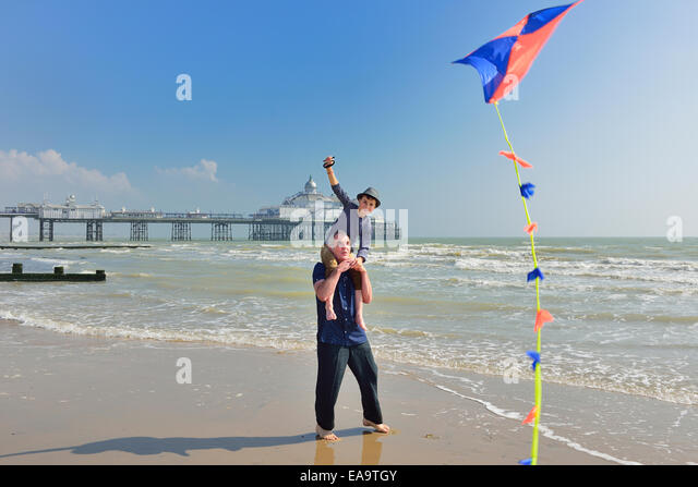Grandfather with grandson flying a kite on the beach at Eastbourne. East Sussex. UK - Stock-Bilder