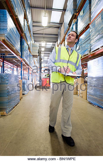 Warehouse manager holding clipboard and checking inventory - Stock Image