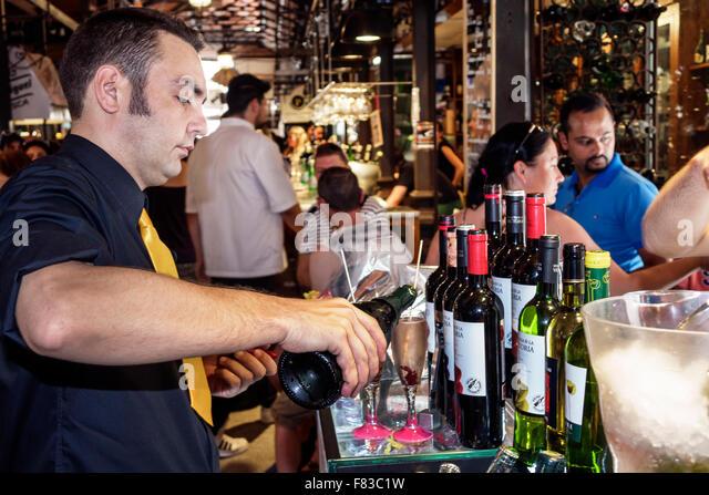 Spain Europe Spanish Hispanic Madrid Centro Mercado de San Miguel market shopping inside man pouring wine steward - Stock Image