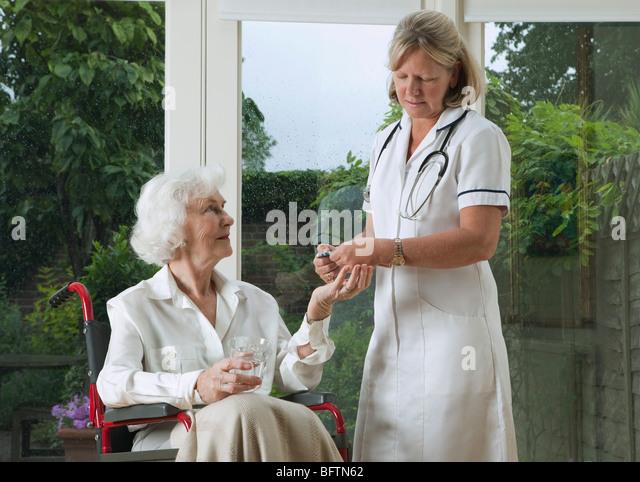 Nurse dispensing medicine to woman - Stock Image