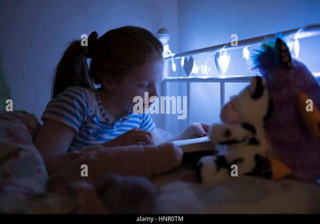 A little girl reading a book at bed time. - Stock Image