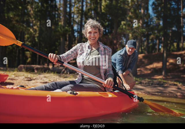 Portrait of happy senior woman in a kayak holding paddles. Woman canoeing with man in background at the lake. - Stock Image