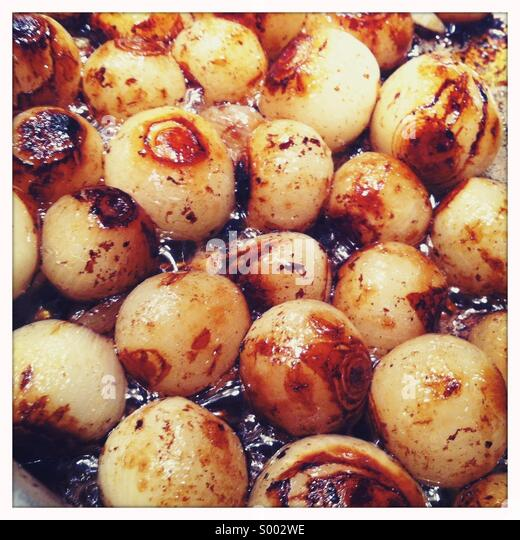 Close-up view of small roasted onions - Stock Image