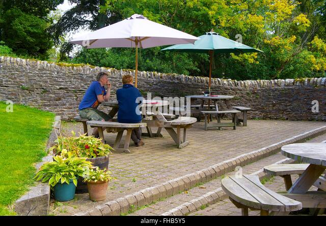 Northumberland. Middle aged couple sitting at picnic table under parasol. The White Monk Tearoom, Blanchland. - Stock Image
