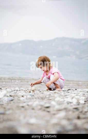 little girl collecting stones on the beach - Stock Image