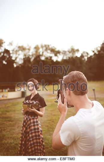 Man taking woman's photography with vintage camera - Stock Image