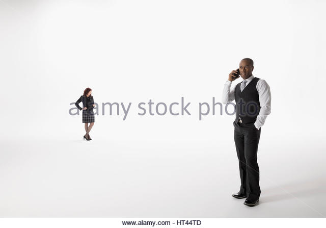 Businessman talking on cell phone and businesswoman texting against white background - Stock-Bilder