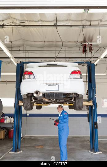 Mechanic checking underneath car on a lift - Stock-Bilder