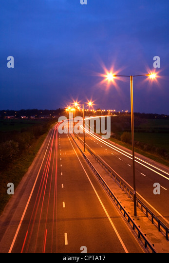 Road at night with traffic trails and street lamps - Stock Image