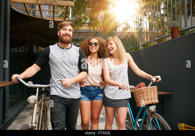 Three young people walking down the street with their bicycles and having fun. Male and female friends with their - Stock Image