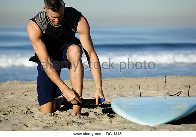 Mid adult man fastening strap on beach for surfing - Stock Image