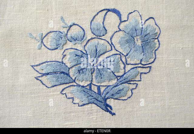 Embroidered satin stitch blue flower on cotton cloth - Stock Image
