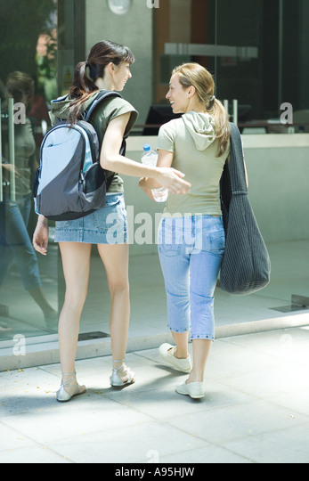 Two young women walking into health club entrance together - Stock Image