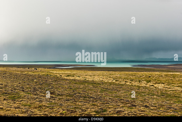 Field and lake in barren landscape, Road 35, Blondulon, Iceland - Stock-Bilder