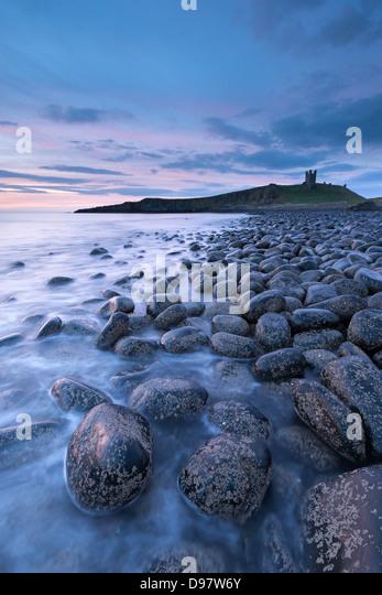 Dunstanburgh Castle at dawn from Embleton Bay, Northumberland, England. Spring (May) 2013. - Stock Image