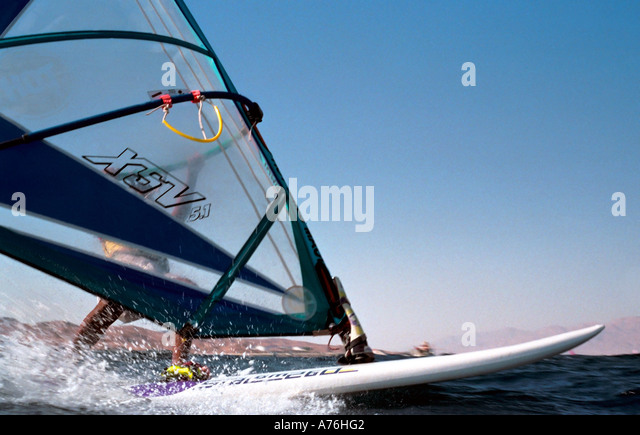 A windsurfer racing along the surface of the sea. This was shot from the water with a nikonos underwater camera. - Stock Image