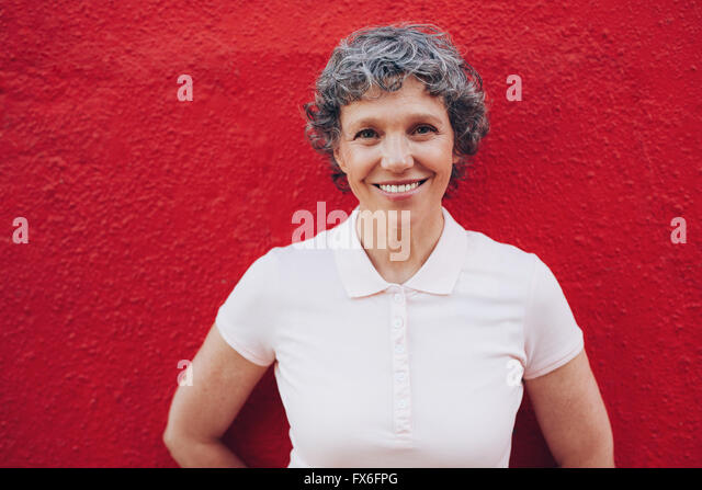 Portrait of senior woman standing against red background. Smiling mid adult female against red wall. - Stock Image