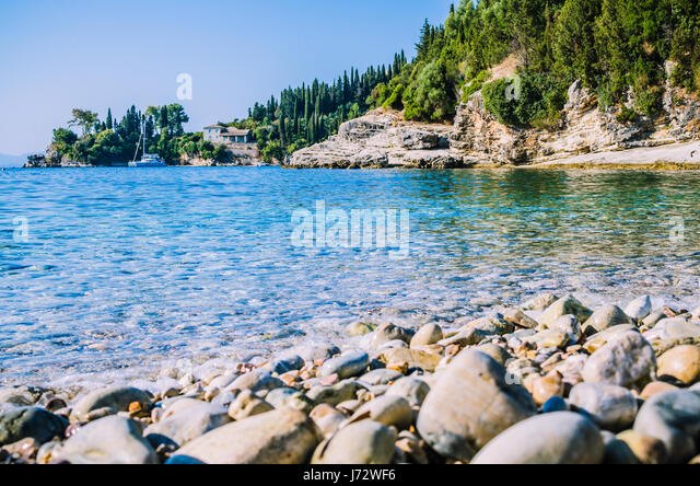 Pebble beach near Kalami with pine and cypress trees and an yacht at anchor in a bay on background. Corfu Island, - Stock Image
