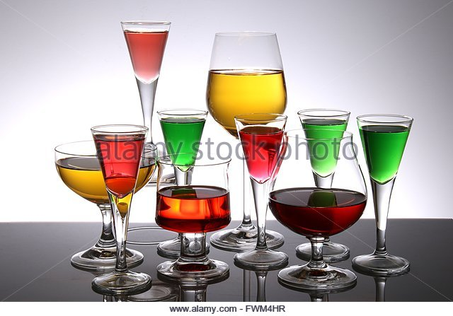 Various Drinks Served In Glasses On Table Against White Background - Stock Image