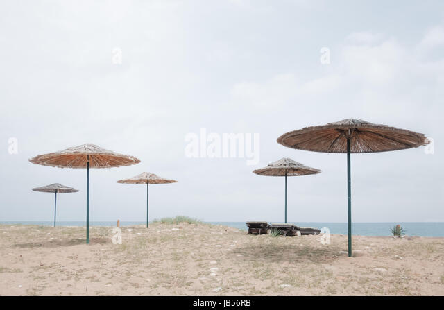 Row of sunshade umbrellas on sea beach. Tranquil view of the Mediterranean sea. Sunny day with clear blue sky. Minimalist - Stock Image