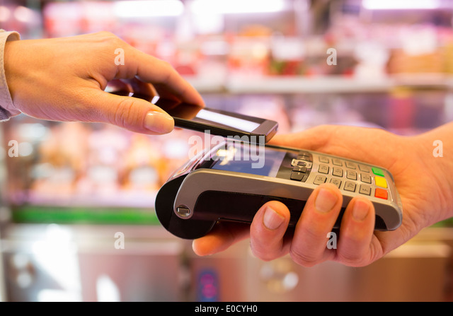Female paying cellphone shop butcher - Stock Image