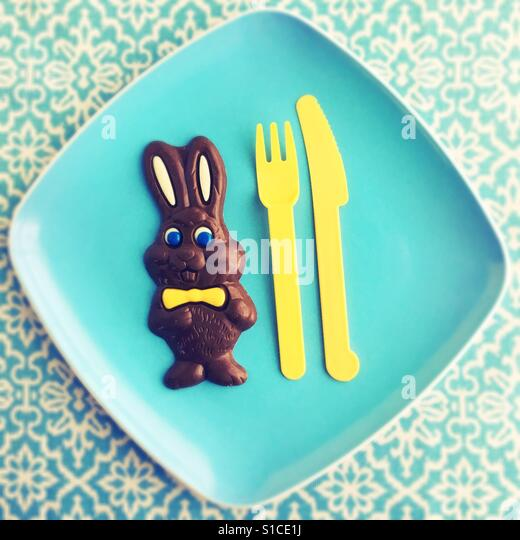 A chocolate Easter bunny on a plate. - Stock Image