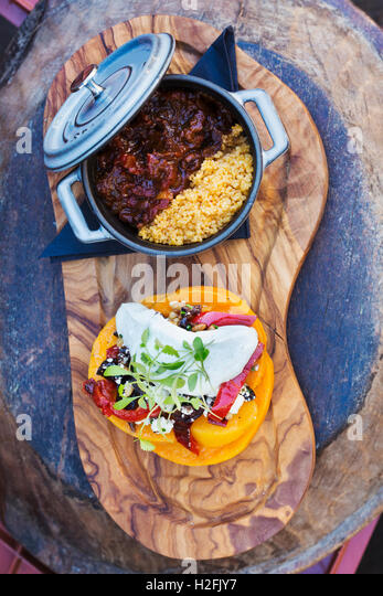 Public house food dishes. Trencher with a small pot of stew and a stack of fresh vegetables and a sour cream garnish. - Stock Image