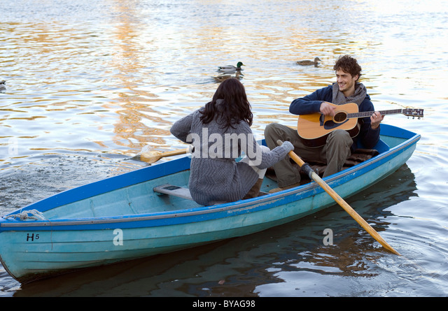 Man playing guitar in row boat - Stock Image