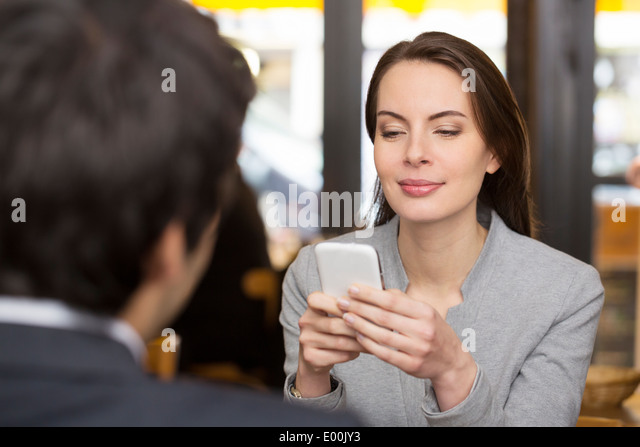 Female male cheerful smartphone dinner bar sms texting surfing web - Stock Image