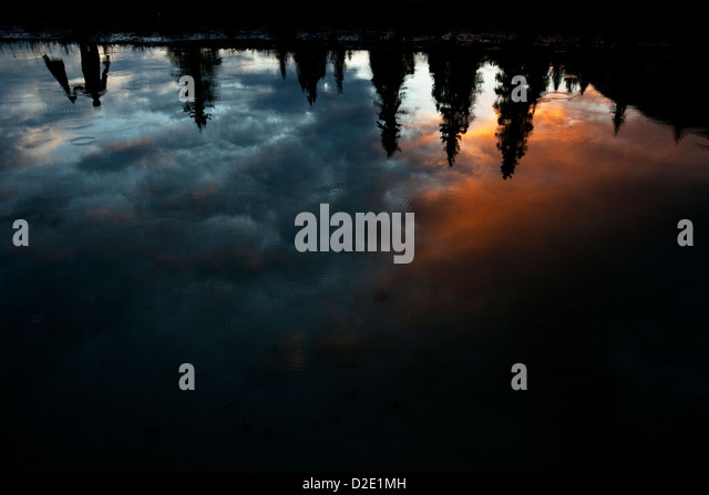 One man reflected upside down in a lake with colorful clouds and rain drops. - Stock-Bilder