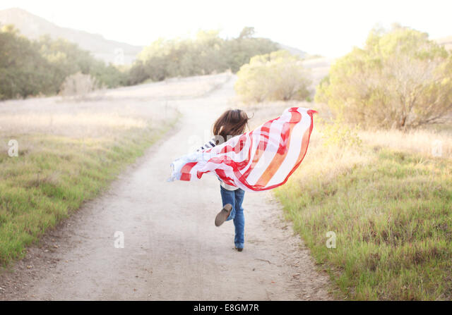 Rear view of Girl running on footpath with American flag - Stock-Bilder