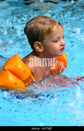 Young boy age 3 swimming kicking - Stock Image