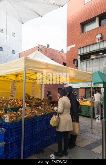Temple Bar Food Market, Meeting House Square, Dublin, Ireland - two young women at stall selling Irish Apples - Stock Image