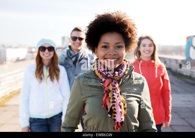 group of happy teenage friends on city street - Stock Image