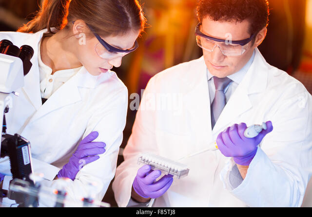 Scientist pipetting. - Stock Image