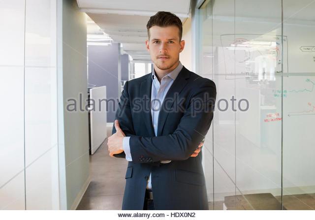 Portrait of serious Caucasian businessman standing in office corridor - Stock Image