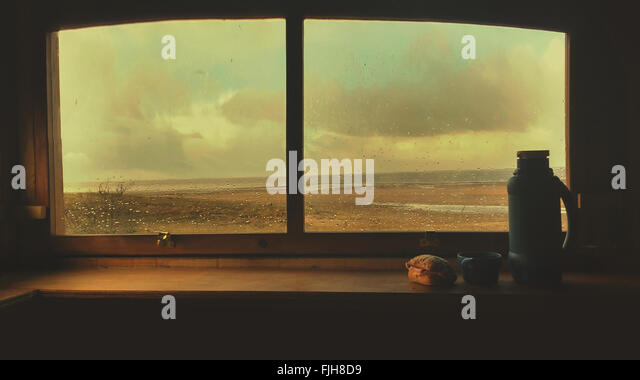 Moody window seat still life with a flask and sandwich - Stock Image