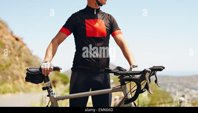 Mid section image of man wearing cycling gear standing with his bicycle, outdoors. - Stock Image