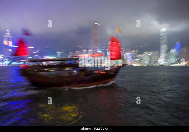 China Hong Kong Skyline and Chinese Junk viewed from Kowloon at dusk - Stock Image