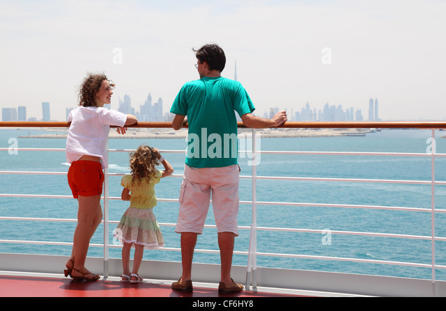 family with daughter standing on cruise liner deck, view from back, city on horizon - Stock Image