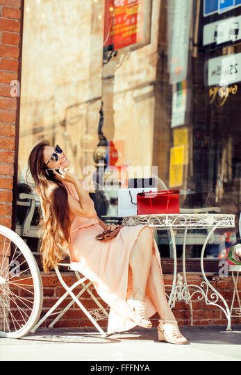 young pretty brunette woman after shopping sitting at cafe outside on street smiling - Stock Image
