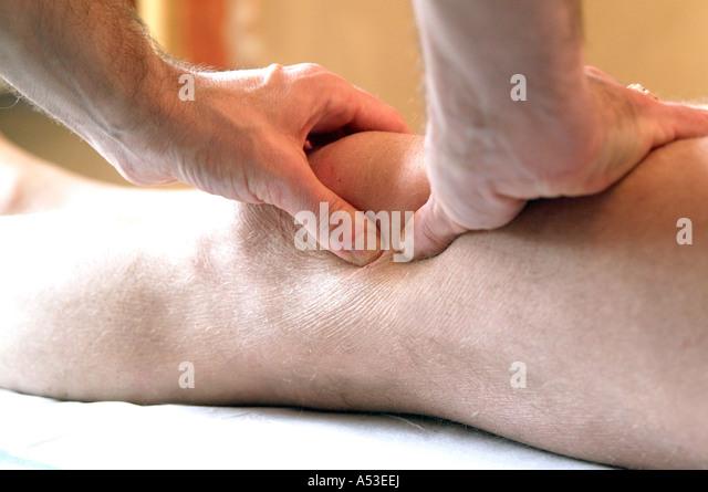British physiotherapist massaging a sporting injury in a health clinic UK London - Stock-Bilder