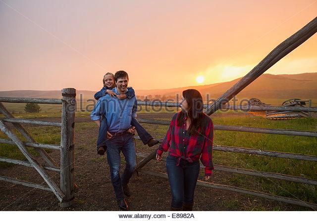 Family walking through pasture gate at sunset - Stock Image