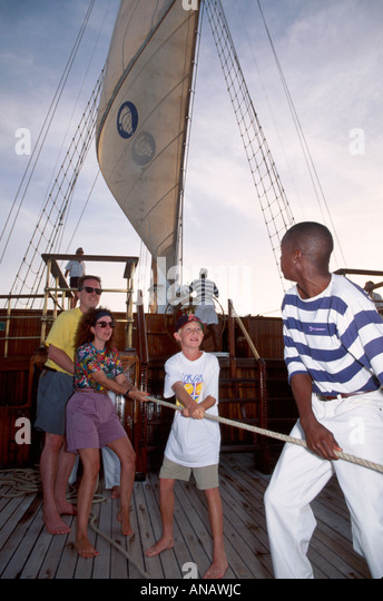 Venezuela Barefoot Windjammer SV Fantome passengers Black man crew raise sail schooner cruise family boy mother - Stock Image