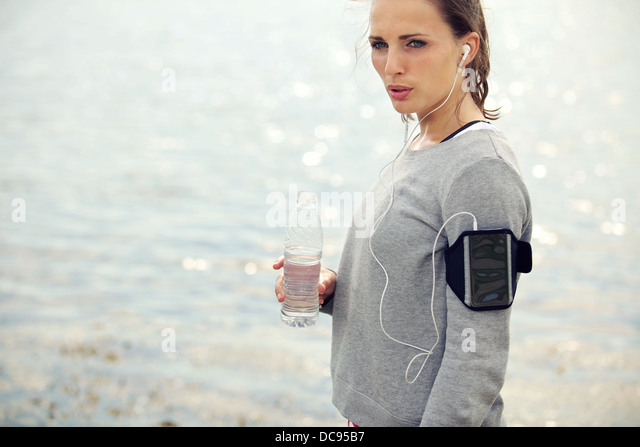 Female runner looking serious while holding a bottled water - Stock Image
