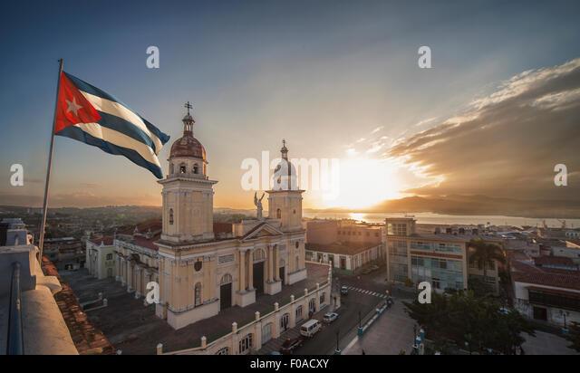 Cuban flag over Plaza de la catedral at sunset, Santiago de Cuba, Cuba - Stock Image